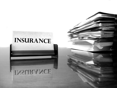 premiums: Insurance card on desk with files Stock Photo