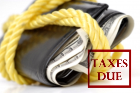 bulging: Bulging wallet tied with rope and a taxes due stamp