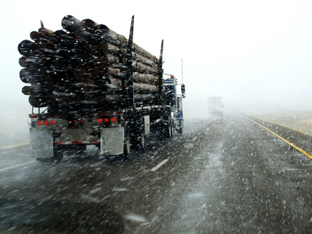truck driver: Semi truck driving down highway during blizzard snow storm