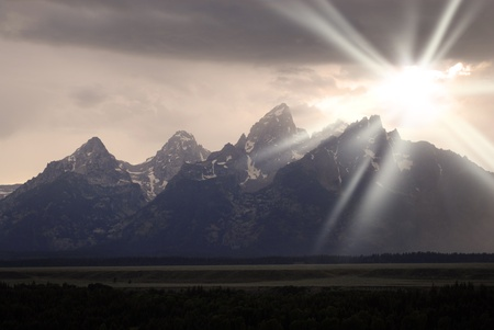 Detail of Tetons Mountains with stormy sky and sun shining through Stock Photo