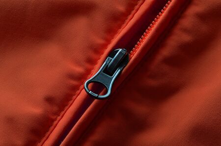 hem: Closeup of zipper on orange or red coat with texture