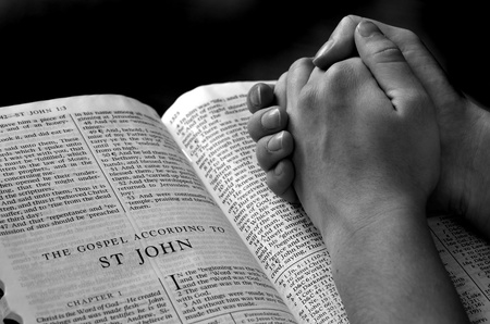 Hands of a person raised together in prayer with bible