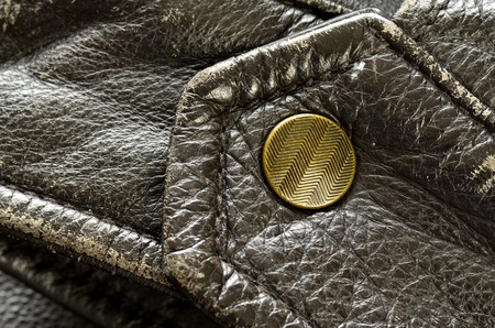 sleeve: Sleeve of leather jacket with detail on the snap or button