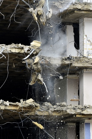 home destruction: Building collapsing or being demolished with debris falling down Stock Photo