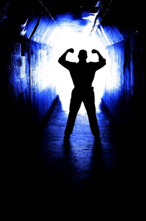claustrophobic: Man at the end of a tunnel with arms raised in victory over fear and becaus eof accomplishment Stock Photo