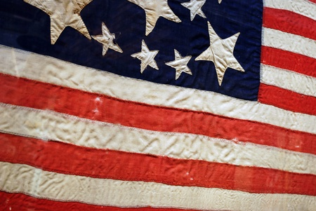 Old weathered antique American Flag with large and small stars photo