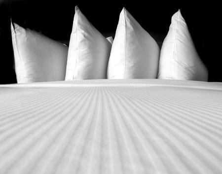 invitando: Grupo de varias almohadas blancas en una cama cómoda