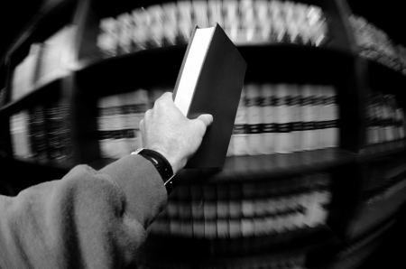 statutes: Hand holding book in an old library in background