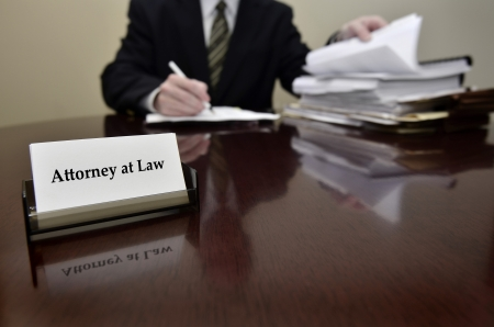attorney: Attorney at Law sitting at desk holding pen with files with business card