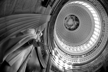 Inside of US Capitol Building with dome and statue of Abraham Lincoln holding document Фото со стока