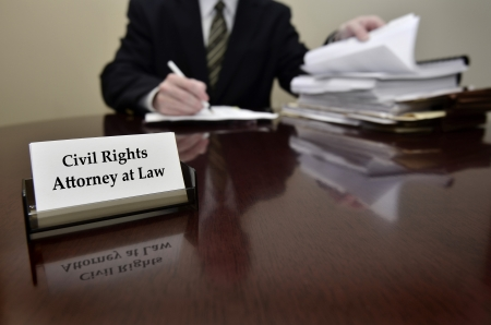 civil law: Civil Rights Attorney at Law sitting at desk holding pen with files with business card Stock Photo