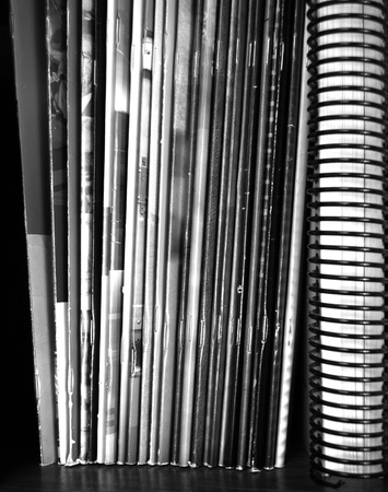periodicals: Closeup of a stack of many colorful magazines on a shelf