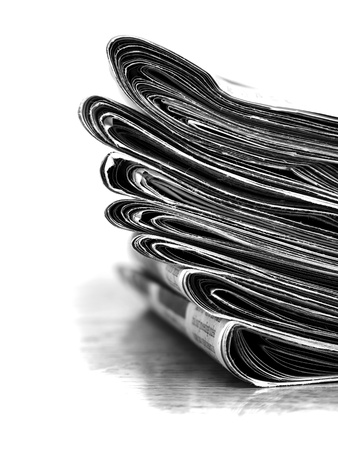 Piled up newspaper isolated on white background photo