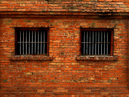Detail shot of an old brick wall with barred windows for security Stockfoto