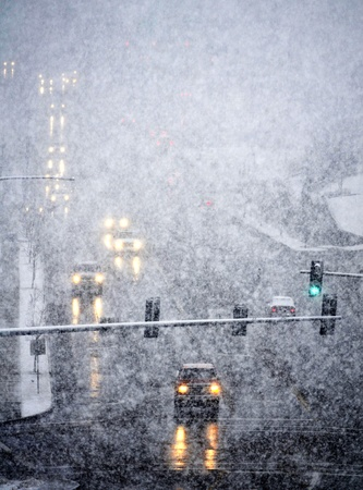 icy conditions: Snowy winter road with cars driving on roadway in snow storm Stock Photo