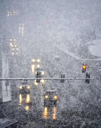 Snowy winter road with cars driving on roadway in snow storm Foto de archivo