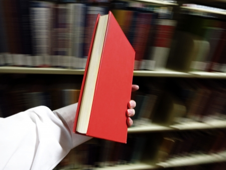 Hands holding a red book with library in background photo