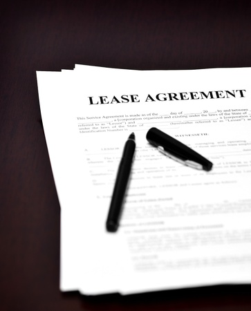 broken contract: Lease Agreement on desk with black pen waiting to be signed