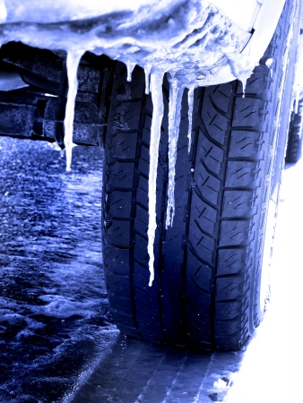 driving conditions: Snowy winter road with tire tracks in snow and tire and icicles Stock Photo