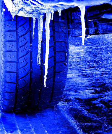 icy conditions: Snowy winter road with tire tracks in snow and tire and icicles Stock Photo