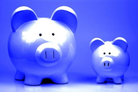 Twee witte spaarvarkens staan op blauwe achtergrond symboliseert besparingen adn geld