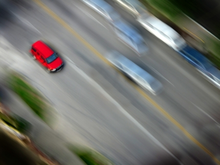 speedy: Speedy red car driving along road with blurred background