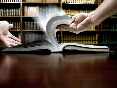 Hands holding an old book with library in background photo