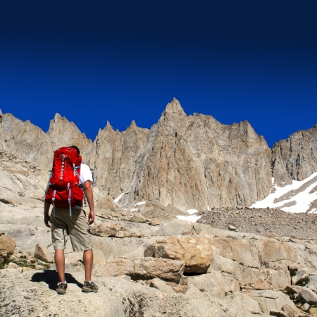 Man standing on rough rock hiking a tall mountain with blue sky                     photo