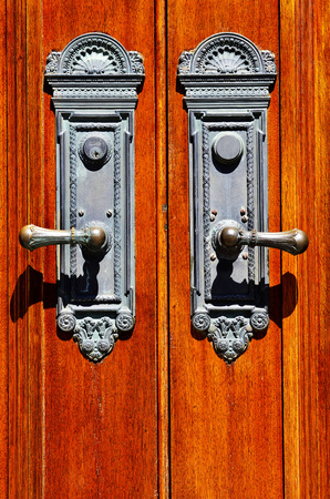 Old iron door handles on worn wooden doors photo