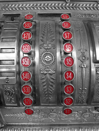 amounts: Detailed closeup of an old cash register with red number buttons for dollar amounts