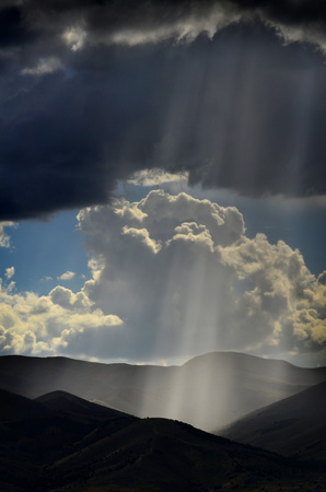 meaning: Sunlight rays from clouds falling on dark mountain range