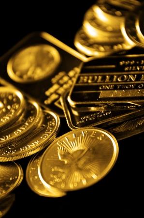 lingotes de oro: Las monedas de oro y lingotes de oro en una pila con fondo oscuro Foto de archivo