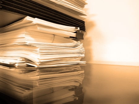 Stacks of papers and business folders on desk against wall Foto de archivo