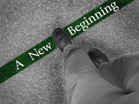 Man walking across a green line with words a new beginning photo