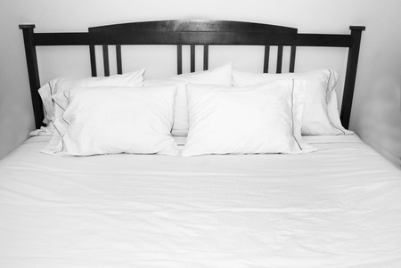 kingsize: Group of several white pillows on a white bed with wooden headboard
