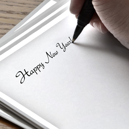 Person writing Happy New Year on card with pen and ink photo