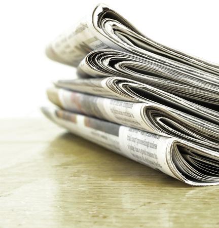 latest: Piled up newspaper isolated on white background Stock Photo