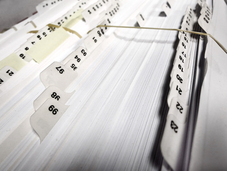 filing cabinet: Several numbered business file tabs on papers and pages in a folder