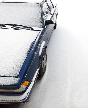 inclement: Car parked on street covered in snow during the winter