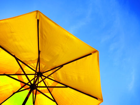 yellow: Yellow umbrella and blue sky symbolizing vacationing in summer