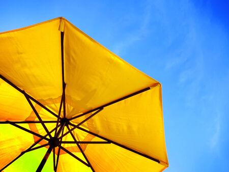 yellow umbrella: Yellow umbrella and blue sky symbolizing vacationing in summer