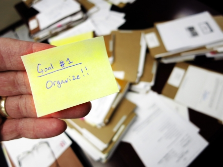Oficina sucio con la mano que sujeta nota diciendo Organízate Foto de archivo