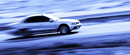 Speedy four door sedan driving along road with blurred background Stock Photo
