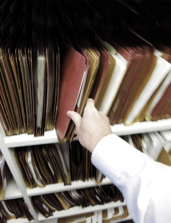 Businessman in office pulling file folder of documents off shelf