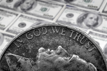 Coin of Silver American Money with words In God We Trust over hundred dollar bills photo