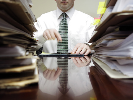 under pressure: Businessman sitting at desk with pad of paper and piles files