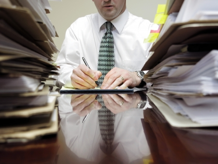 Businessman sitting at desk with pad of paper and piles files photo