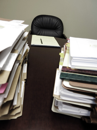 Desk with pad of paper and piles files photo