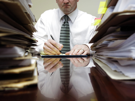 cubicle: Businessman sitting at desk with pad of paper and piles files