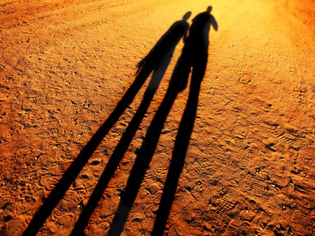 Shadow of two people holding hands walking down a dirt road together